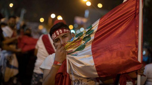 joven en la protesta con una bandera de Perú