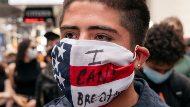 """Un manifestante con una mascarillas con la bandera de Estados Unidos y la leyenda:""""No puedo respirar""""."""