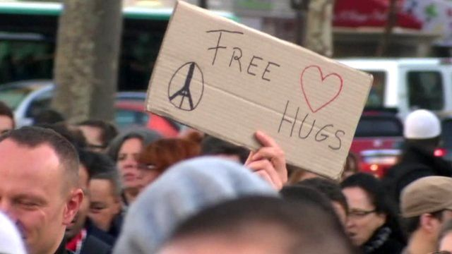 Cardboard sign with 'Free Hugs' written on it