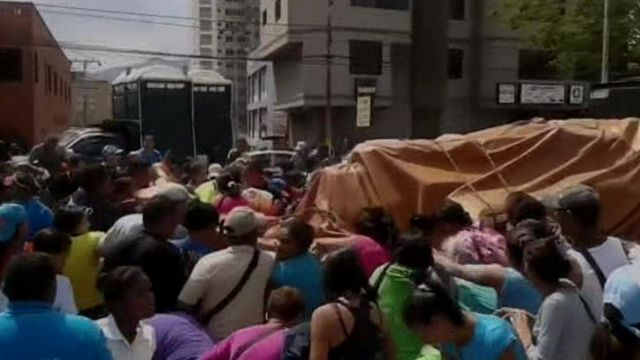 People surround a truck delivering flour in Puerto la Cruz