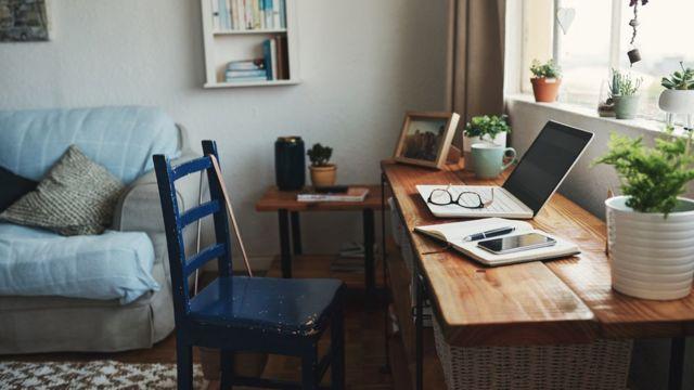 Sala de uma casa com computador, caderno, celular, caneta e óculos