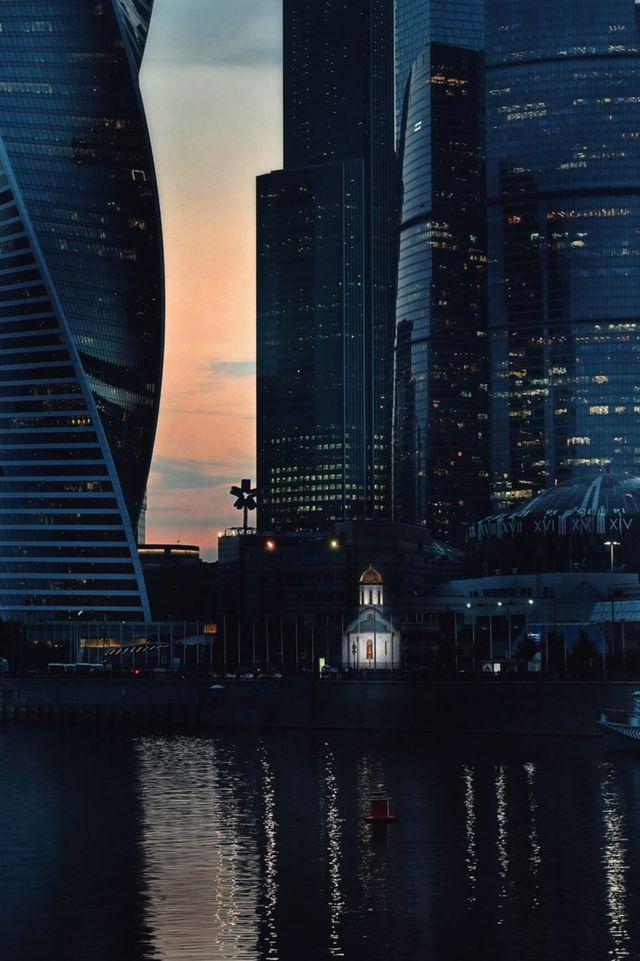 俄国首都莫斯科,林立的摩天大楼中矗立着一座灯光温暖的教堂。