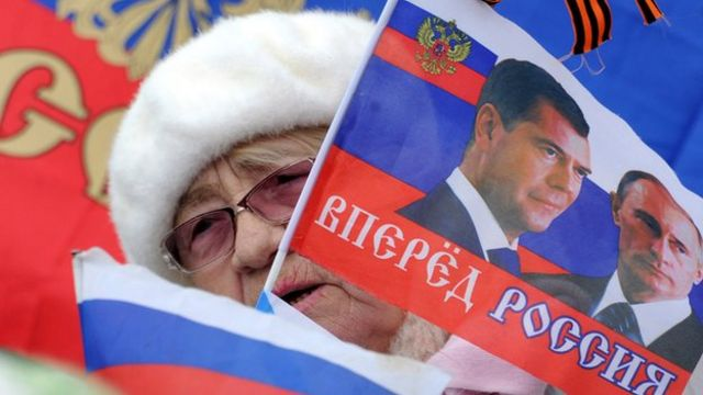 A woman holds a flag depicting Russian President Vladimir Putin and Russian Prime Minister Dmitriy Medvedev during a rally in Sevastopol on 17 March 2014.