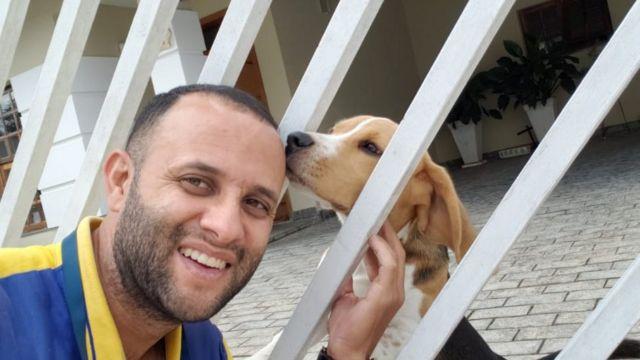 Angelo e um cachorro que mora em uma das casas de sua rota