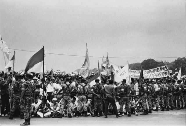 circa 1965: Indonesian troops bar a crowd of flag-waving students from the approach to president Achmed Sukarno's summer palace at Bogor in Indonesia following the abortive Communist coup of 1965.