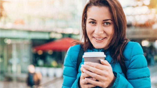 Mujer con un café en las manos en un día de invierno.