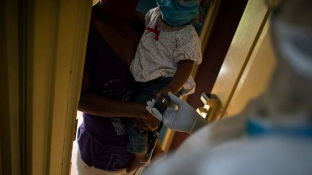Profissional de saúde faz teste em criança, com máscara em colo de adulto