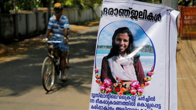 """A man pedals his bicycle past a poster of Anzi Ali Bhava, who was killed in Friday""""s mosque attacks in New Zealand, in Kodungalloor town in the southern state of Kerala, India, March 17, 2019"""