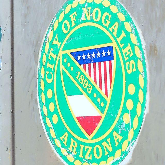 Escudo de Nogales con la bandera de EE.UU. y México