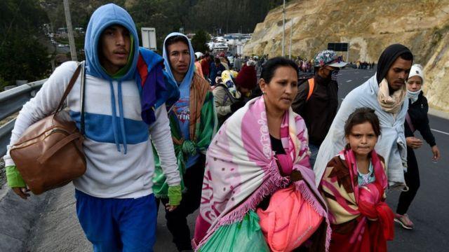 Migrantes venezuelanos caminhando em estrada