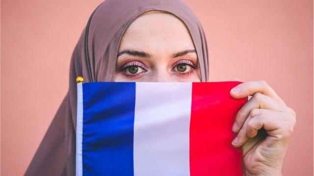 فرنسية مسلمة تحمل علم بلادها