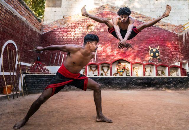 Dos hombres realizan una secuencia de artes marciales, uno enarbola un cuchillo mientras el otro da un gran salto en el aire para esquivarlo