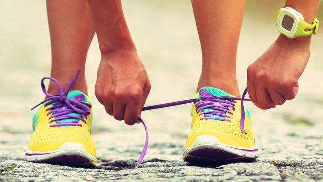 Mujer atándose los zapatos