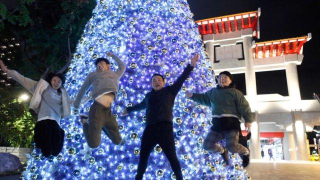台湾的一些年青人在圣诞树前玩耍摆拍