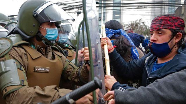 Mapuche en frente de miembros de seguridad chilenos.