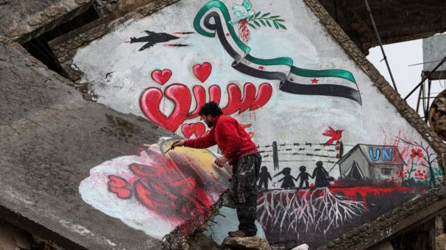 """A man draws a slogan in Arabic reading """"we still want freedom"""" as part of a graffiti mural commemorating the ninth anniversary of uprising that led to the Syrian conflict (March 15), showing a dove holding an olive branch in its beak flying over a Syrian opposition flag in the shape of the eastern Arabic numeral """"9"""" while being targeted by the silhouette of a military aircraft with the Arabic word """"years"""" below as silhouettes of children stand by a border fence and a tent with the letters """"UN"""", drawn on the collapsed roof of a heavily damaged building in the town of Binnish in the northwestern Idlib province on March 13, 2020. ("""