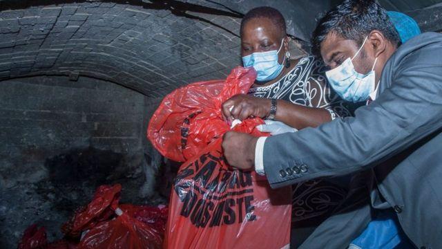 马拉维卫生部长孔比兹·奇蓬达(Khumbize Chiponda)(左一)帮忙将疫苗放入医院的焚烧室。(photo:BBC)