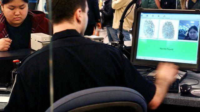 Agente de inmigración en EE.UU. verifica las huellas digitales de una pasajera