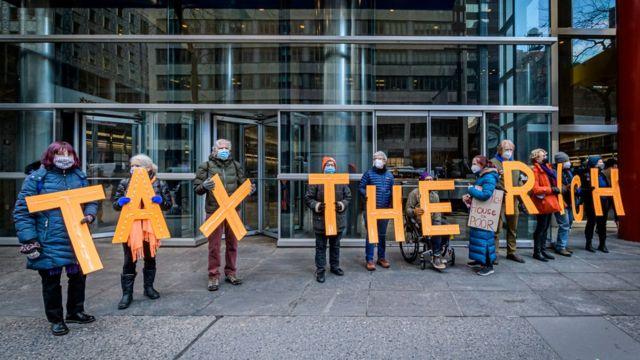 Manifestantes con carteles exigiendo un alza de impuestos a los más ricos.
