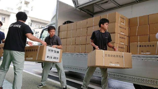 pessoas colocam caixas em caminhão