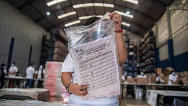 Uma trabalhadora eleitoral preparando cédulas para voto