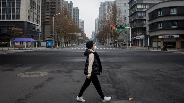 Mujer con mascarilla en Wuhan