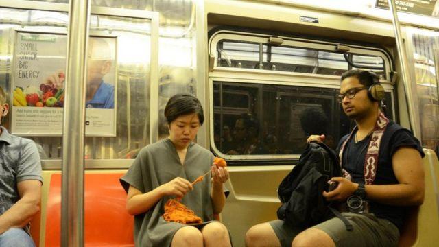 Mulher faz tricô sentada em vagão do metrô