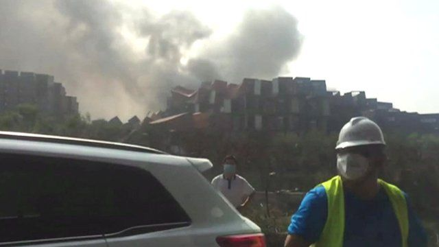 Debris and smoke at explosion site in Tianjin