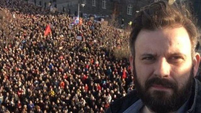 футболист Рагнар Ханссон на фоне толпы протестующих