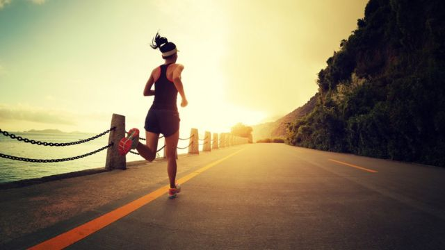 Young female jogging long a road overlooking the sea and mountains
