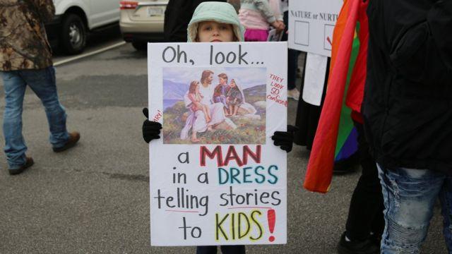 criança com cartaz em apoio às drag queens