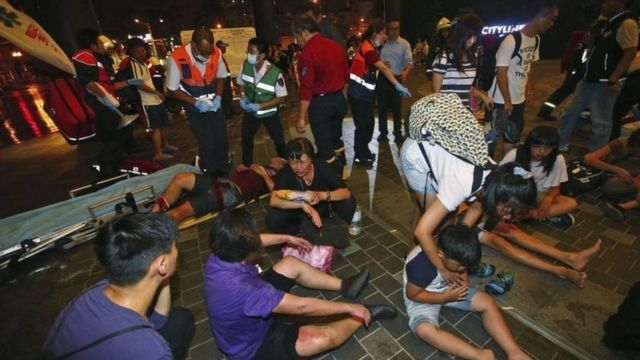 Injured people are helped by emergency rescue workers outside a station after an explosion on a passenger train in Taipei, Taiwan, Thursday, July 7, 2016