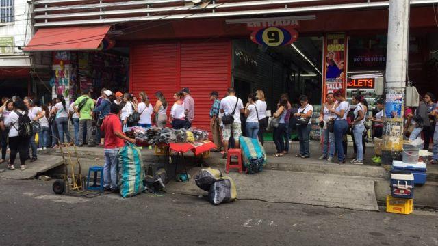 Venezolanos hacen fila para cambiar bolívares a pesos colombianos.