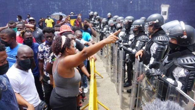 Migrantes frente a policías en Tapachula