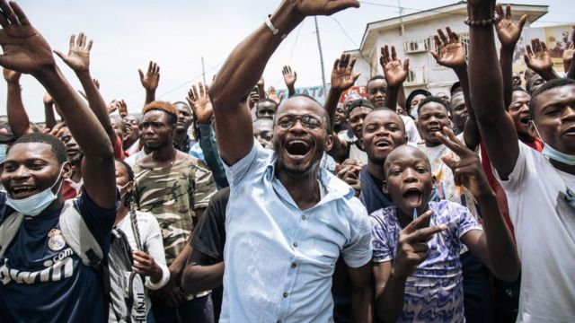 Supporters of incumbent Congo President Denis Sassou Nguesso (not visible) wave to the president after he cast his ballot in Brazzaville on March 21, 2021.