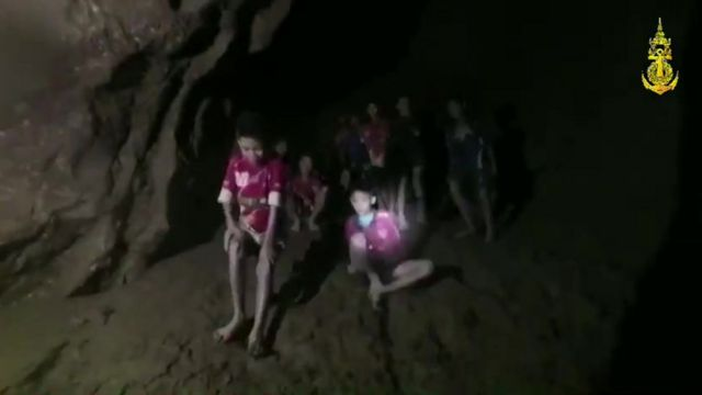 Tham Luang cave, Thailand. Boys trapped in a cave are seen sitting on a dry piece of land in a dark cave lit by a torch