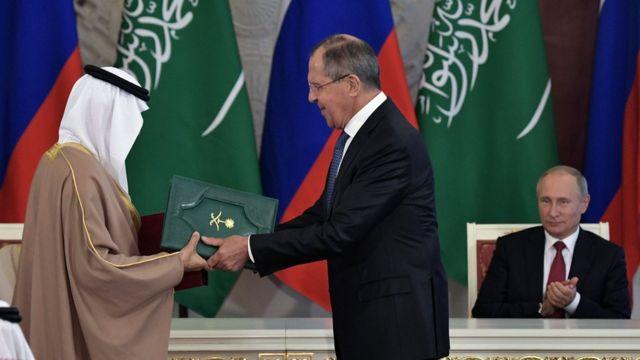 Suudi Arabistan Enerji, Endüstri ve Maden Kaynakları Bakanı Halid El-Falih ile Rusya Dışişleri Bakanı Sergey Lavrov imzaladıkları metinleri birbirlerine verirken Rusya Devlet Başkanı Vladimir Putin ikiliyi alkışladı