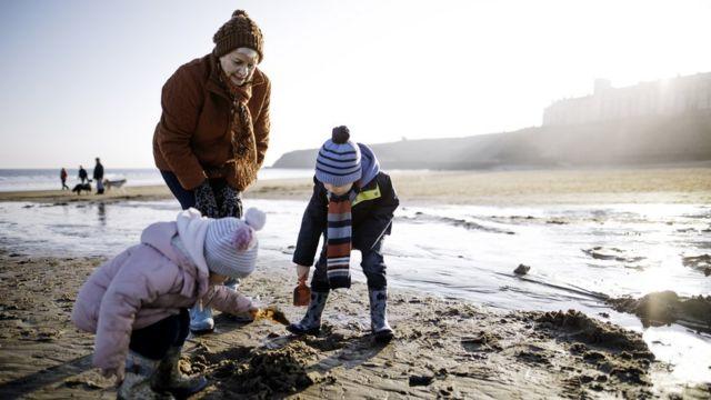 Abuela jugando en la playa con sus dos nietos pequeños.
