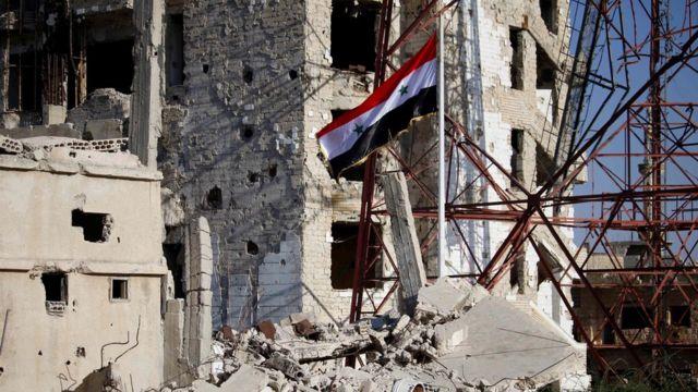 ダラアの町の損傷した建物の中心に、軍はシリア国旗を掲げた