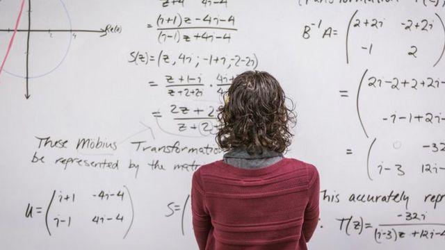 Mulher olhando para fórmulas matemáticas