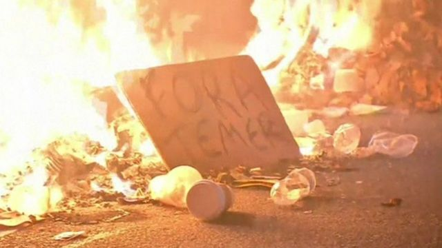 """Flames burnt around signs propped up in the road reading """"Out with Temer"""""""