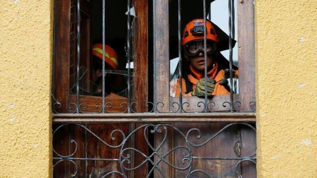 Bomberos en las ventanas dañadas tras la explosión.