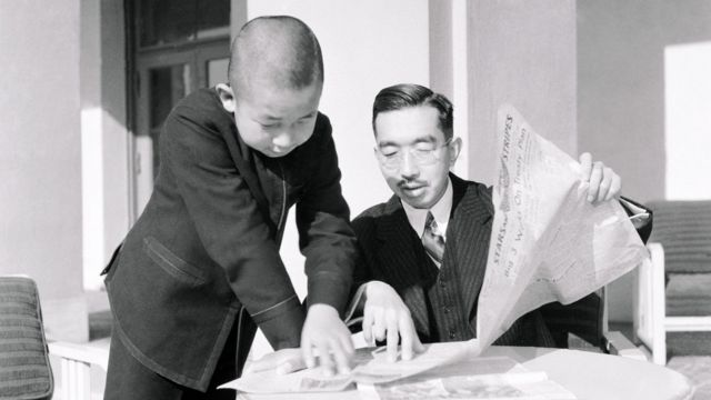 Emperor Hirohito and Prince Akihito reading a newspaper
