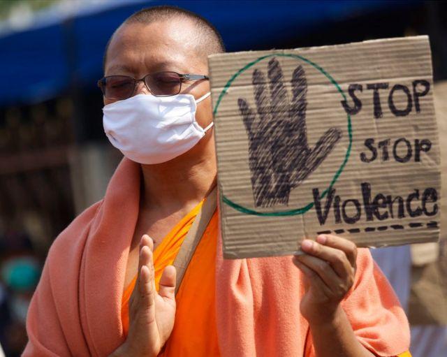 """Bir Budist keşiş """"Şiddeti durdurun"""" yazan bir pankart taşıyor."""