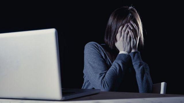 Mujer tapándose la cara frente a una pantalla.