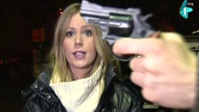 TV reporter speaking into camera, a man waves revolver in front of her