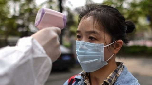 """A man wearing a protective suit checks a woman's temperature next to a residential area in Wuhan, in China""""s central Hubei province on April 7, 2020."""