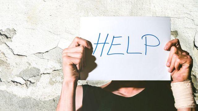 Mujer con un cartel tapándole la cara con la palabra ayuda.