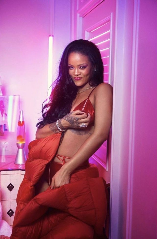 Rihanna smiles in her latest collection for Savage X Fenty in red satin bra set and a red long puffer jacket
