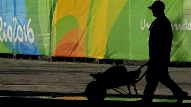 Trabajador pasa frente a la villa olímpica en Río